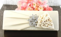 """Wedding Clutch Wedding Purse Bridal Clutch by goddessdesignsgems, $54.00 """"Absolutely beautiful design"""" this gorgeous satin clutch in a shimmering creme/ivory color features a pleated flap embellished with a stunning crystal silver brooch nestled next to a gorgeous satin three flower rosette for a very rich & elegant look with. Magnetic clasp closure under the front flap easily secures items inside. Inside Interior has a fabric lining with slide pocket and a concealable 20"""" silver chain."""