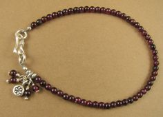 This is a red garnet bracelet with dangles.  The stones are natural red garnet. The catch and the small charm are extremely pure solid fine silver