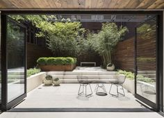Julie Farris Manhattan courtyard garden. In Manhattan, an airy hedge of bamboo provides screening at the garden's perimeter while a pared-down palette of green and white focuses the eye on the center of the space. Photograph by Matthew Williams.