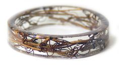 Designer Sarah Smith creates beautiful resin bracelets. Rings are made from dries and frozen flowers, plants and tree barks and then embedded in transparent resin. A manufacturing processus long of three weeks to come to the final result.