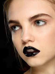 An Impactful Pout - Once upon a time black lipstick was considered goth–London-based fashion label Giles shows us that those days are behind us. Give a dewy, fresh complexion some edge with a shiny, black lipstick. Wear the bold lip with equally bold brows and a natural eye shadow.