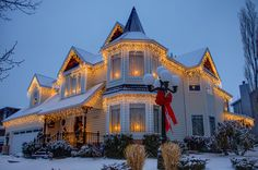 Christmas lights ideas - Hang clear icicle lights on a Victorian house, red bow on lamp post. Beautiful