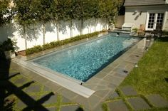 Traditional rectangular lap pool with raised spa and an automatic cover.