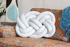 You only need a 6 by 5 1/2-yard piece of fabric and a 32-ounce bag of stuffing to create your own fabric knot pillows.