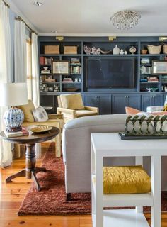 Dark blue paint on built-ins. Love the brass lighting and drapery hardware