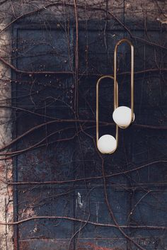 The lamps' spherical handblown glass diffusers are suspended in brass, copper and satin black or textured white metal frames of varying lengths.