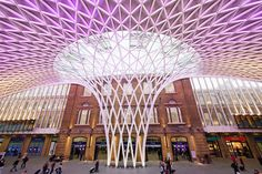 The historic section of King's Cross was designed by architect Lewis Cubitt and completed in 1852. At the time, its two train sheds' glass roofs were considered cutting-edge, although their laminated-timber beams were replaced with steel girders, and their two platforms and 14 tracks quickly fell short of demand. A new edge has been honed with a 15-year, $650-million renovation project that has as its most prominent feature this new concourse designed by John McAslan. Covering a new ticket…