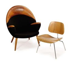 A GROUP OF TWO MODERNIST CHAIRS, SECOND HALF 20TH CENTURY, comprising: a Scandinavian grey wool and leather upholstered club chair and an Eames molded walnut 'LCM' chair, produced by Herman Miller, of recent manufacture 40½in. (103cm.) high, 34½in. (87.5cm.) wide, 25in. (63.5cm.) deep, the larger, the club chair (2)