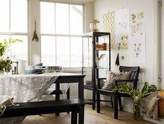 Romantiskt inredd veranda med inslag av rått trä och industridetaljer med ÄNGSÖ svart utemöbler