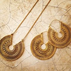 This brass necklace and earrings set is modeled on an antique Rajasthani design which honours the hindu sun god Surya. The filigree and dot work is