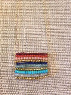 """This beautiful Boho-Chic pendant necklace features layers of colorful gemstone beads: garnet, coral, peach coral, lapis, light apatite, turquoise, moonstone, and gold pyrite. The gold-filled chain necklace is 18"""" in length and the pendant is approximately 2 1/2 inches wide."""