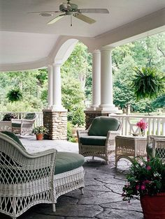 this porch is HUGE! I love the stone floor and stacked stone columns and white wicker furniture everywhere. You would find me here a quite a lot!