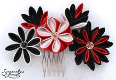 "Amaterasu: Featuring a set of blossoms in black, pure white, and bright red, this artful and unique tsumami kanzashi portrays a traditional color scheme in an eye-catching, edgy style. With two leaves in complementing colors and pearl and gemstone centers, 'Amaterasu' is mounted on a comb for easy wear and measures approximately 4.75"" x 3.5""."