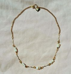 A simple 18 inch gold plated necklace with white sea shell stones and a gold heart charm.