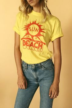 Most amazing 1980s deadstock vintage vacation t-shirt featuring one-color orange graphic saying Sun of a Beach across front. Printed on a 50/50 cotton poly blend Sportswear tee, never washed or worn, in perfect new old stock vintage condition, an actual dream tee with such an original graphic. Pair tucked in to mid rise jeans.  Era: 1980s  Fits Like: Medium  Bust: 36 Inches Waist: 38 Inches  Total Length: 28 Inches  Condition: Pristine vintage  Model is 59, Bust - 32, Waist - 25, Hips -...