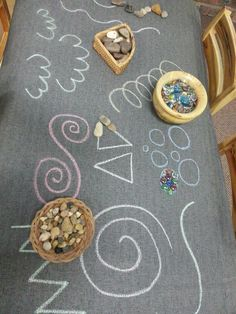 Invitation to explore pattern and shape. Chalk drawings on off-cut vinyl,  pebbles rocks and glass beads.