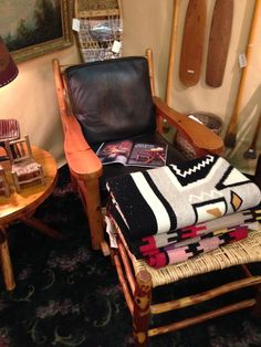 Rittenhouse paddle arm chair and pile of Navajho rugs, Christibys show booth