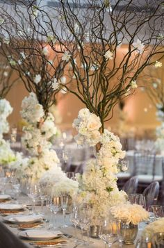 rustic white flowers tall winter wedding centerpiece idea via john cain photography / http://www.deerpearlflowers.com/unique-wedding-centerpiece-ideas/3/
