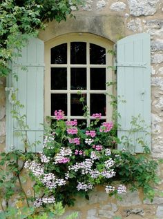Stone House with Vintage Shutters and Geraniums in a Window Planter....