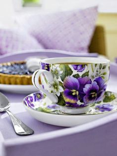 Beautiful Purple Flower Tea Cup sitting on a Purple Tablecloth.