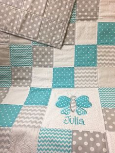 "This generously sized baby quilt measures approximately 36"" X 54"". The patchwork quilt top is made from 100% cotton and is layered with 100% cotton batting that has been machine quilted and bond for longevity. Colors shown: aqua, gray and white. Colors can be changed. In note"