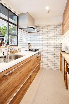 ウッディな面材のシステムキッチンに、サブウェイタイルをコーディネート。床はタイル風のクッションフロアで、見た目とコストとメンテナンスの三者を両立。(Yono House)
