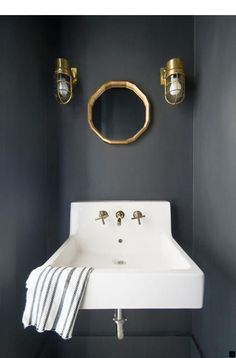 This small black-and-white powder room features a wall mount sink with a polished nickel faucet boldly standing out against matte charcoal black surrounding walls. Charcoal Bathroom, Charcoal Walls, Black Walls, Charcoal Black, Black White, Black Powder Room, Powder Rooms, Wall Mounted Sink, Downstairs Toilet
