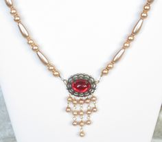 """Lady Caterina is a gorgeous, rich necklace and earring set, featuring bronze glass pearls and a glowing ruby red glass cat's eye cabochon set in an antiqued filigree. Another limited edition set that will enhance all your special outfits. You'll get lots of attention at the Faire in this dazzling set! The necklace measures a generous 20""""; the matching earrings hang 1 1/2"""" below surgical steel ear wires. Camelot Collection $35"""