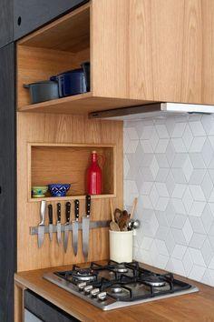 Depurador embutido no móvel alto, nicho lateral e ímã para facas nesta cozinha onde prevalece a madeira.: