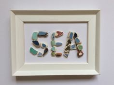Beach pottery Sea motif framed picture. Small pieces of sea pottery in mosaic lettering. Framed in a 4 X 6 frame. There is no glass in the frame. The picture can be wall mounted or free standing. All the pottery pieces and have been lovingly collected from the beach near our home in the east of Scotland. The fragments have been in the sea for many years, broken and washed smooth by the waves.