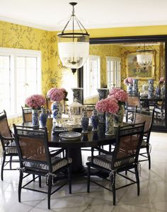 Gorgeous dining room with black cane chairs, blue and white striped cushions, blue and white porcelian, yellow floral wallpaper, and marble floors