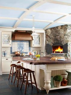 Old-English Influence  To get the look of an English country kitchen, this kitchen starts with cream-color cabinets. A wood-topped island and saddle-seat barstools add contrast, while the copper hood, stone fireplace, and flooring add organic touches. A mural backsplash behind the range introduces a hint of color.