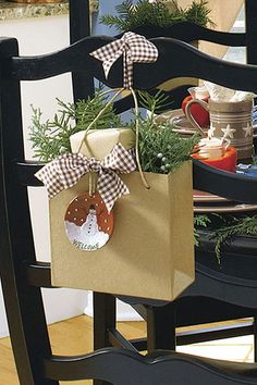 Presents or party favors in paper gift bags,  with a few sprigs of greenery, an ornament and ribbons at a ladderback chair