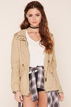 A woven utility jacket featuring a zipper and button front, mock neck, drawstring hood and waist, two front button pockets, two faux chest pockets, and long sleeves.