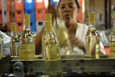 La obrera le coloca la etiqueta a las botellas