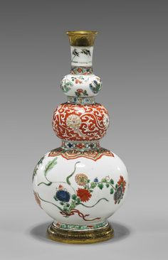 """Antique, Chinese Kangxi Period, enameled porcelain vase; of triple-gourd form, decorated with multi-colored scattered flowers to the top and bottom section, the middle section with coral red scrolling blossoms; with later gilt bronze rim and foot mounts; H: 9 1/2"""""""