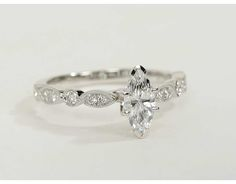 Vintage-inpired, <3   wedthis diamond engagement ring is crafted in 14k white gold and features petite diamonds set in a marquise and dot pattern with milgrain edges to frame your center diamond. Setting includes 1/5 carat total diamond weight.