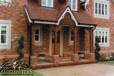 Oak beams with curved braces and brick piers make an attractive canopy on the front of this house.