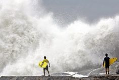 Surfers watch the waves from Mirante point as heavy surf pounds a section of Leblon beach in Rio de Janeiro