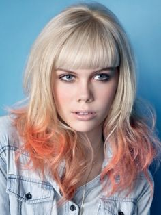 Long straight blonde with curly dip dye orange ends and straight cut bangs hairstyle