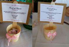 Composizione tavoli. Realizzato con un cestino in legno biologico contenente dei confetti e su cui è incollato un nastro rosa. Una stecca per gelati su cui è applicata una bandierina in carta da imballaggio e semplice carta bianca stampata.