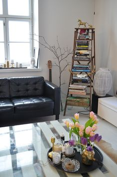 I love this living room. . Black leather couch,  using the ladder for books,  beautiful coffee-table.