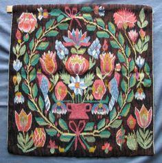 Flamskvävnad med motiv av en röd urna med en stor blomsterbukett flankerad av två blå fåglar i bladkrans. Olika blommor utanför kransen, större i hörnen. Något dämpad färgskala mot brunsvart botten. Varpen knuten med langett och därefter flätad mot baksidan där trådarna är nersydda två och två. Monterad att hänga.
