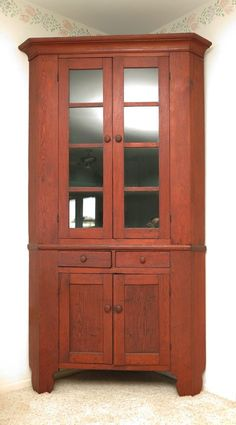 "AMERICAN COUNTRY PINE CORNER CUPBOARD: 8 panel glass top doors with 3 interior wood shelves. Base with 2 drawers over 2 doors. Shaped front feet. 85"" h. x 47 3/4"" x 24""."