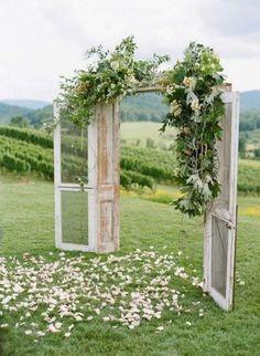 Portes en bois avec feuillage et lit de pétales pour une cérémonie de mariage en plein air