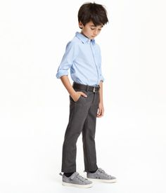 Suit pants in twill with wool content. Adjustable elasticized waistband with concealed hook-and-eye fastener and zip fly. Creases, side pockets, and welt back pockets with button.