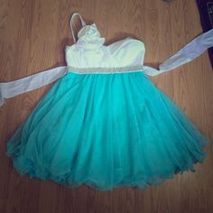 Never worn Homecoming or Prom Dress. Size 6 Bought this dress for a homecoming dance, but decided on another dress. One shoulder white and Aqua dress. Hits mid thigh and is very flattering!! Full tulle skirt and flower accent on the since shoulder strap. Dresses One Shoulder