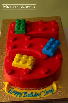 Block Number Cake #83Hobbies by Michael Angelo's Bakery | This cake is shaped into the number five and then iced in red fondant. Small round cut-outs were added to make it look like a real Lego. Smaller blocks were also added on top for some more decor.