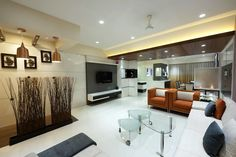 Classy ambiance of living room space .Furnished with different sofa elements having cushions . The front wall having LCD unit designed with a wooden paneling and wall hung shelf cum storage drawer unit . Glass center table placed along with sofa units .Above decent ceiling with down lights .A corner space with vertical decorative planters and above raised ceiling with hanging lights and down lights .