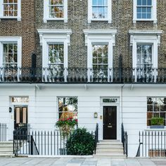 Restored grade II listed Chelsea townhouse, in London. black railings, brickwork with painted sash windows